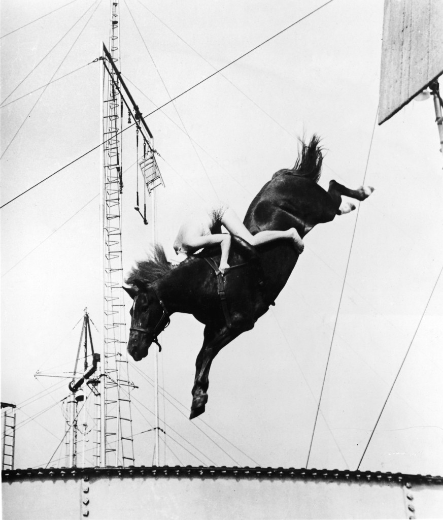 A male circus performer holds tight while riding atop a horse for a stunt high-dive into a swimming pool, 1930s. (Photo by Frederic Lewis/Getty Images)