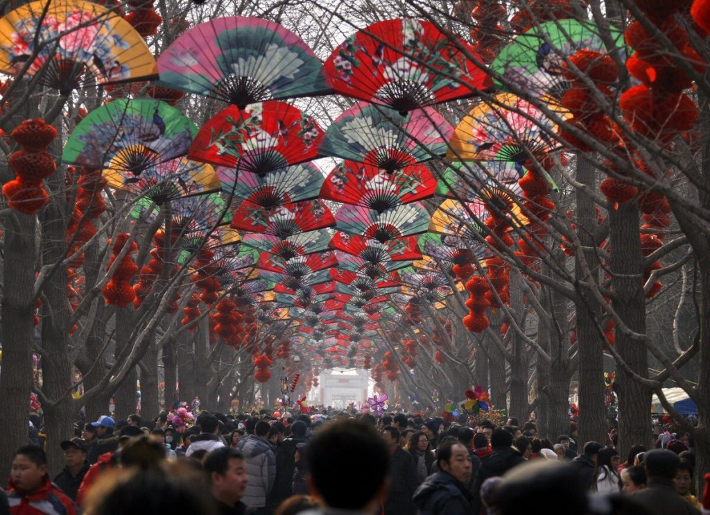 large-crowds-walk-under-a-row-of-trees-decorated-with-fans-and-red-lanterns-at-a-temple-fair-celebrating-the-chinese-new-year-in-beijing (1)