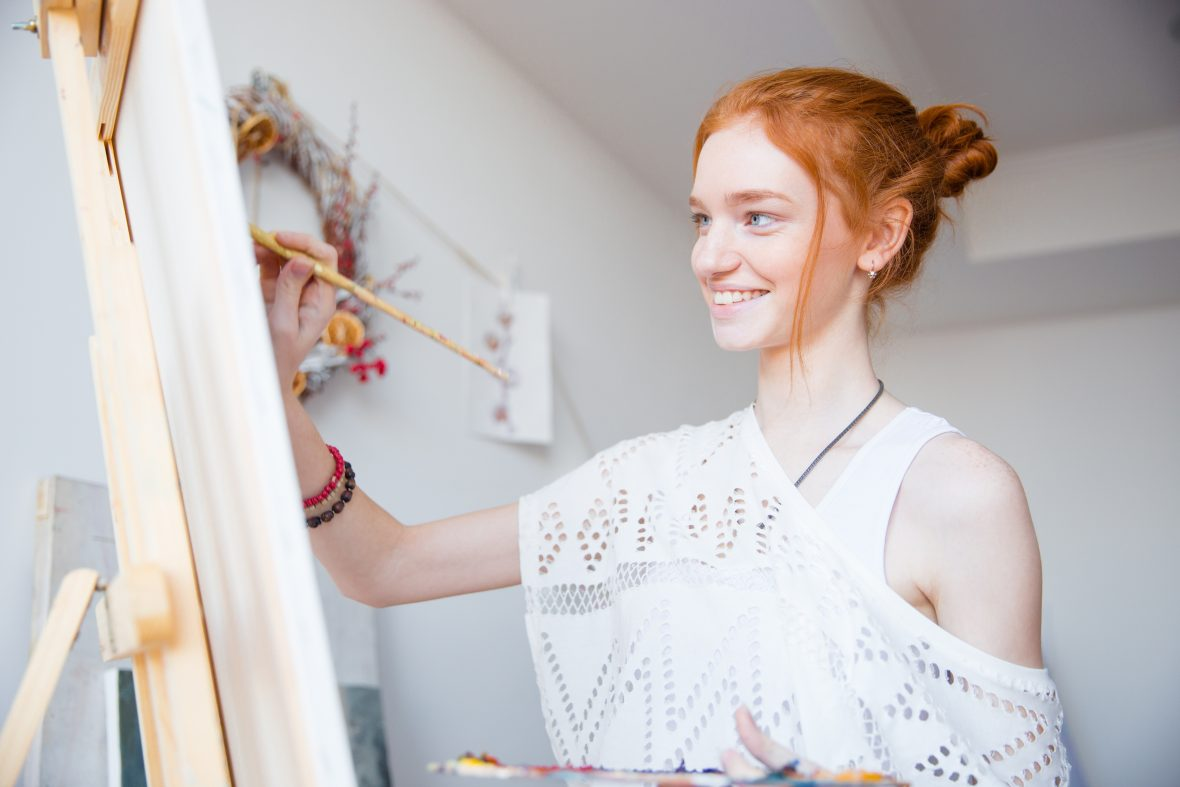 Smiling attractive woman painter with red hair painting on canvas