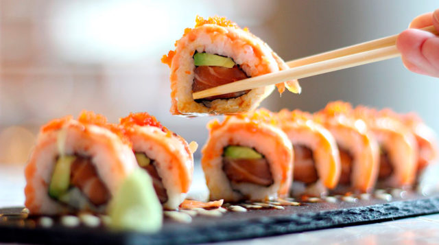 cropped-image-of-person-holding-sushi-at-table-royalty-free-image-691103589-1536344826